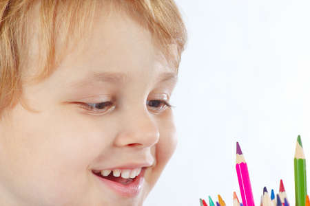 Little smiling boy looks on color pencils on a white background photo