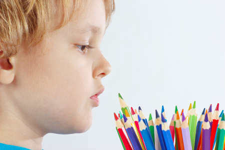 Young cute boy looks on color pencils on a white background photo