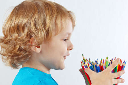Little child looks on color pencils on a white background photo