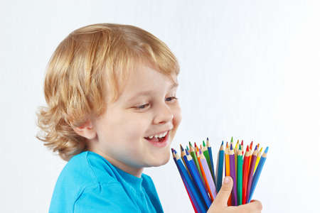 Little cute child with color pencils on a white background photo