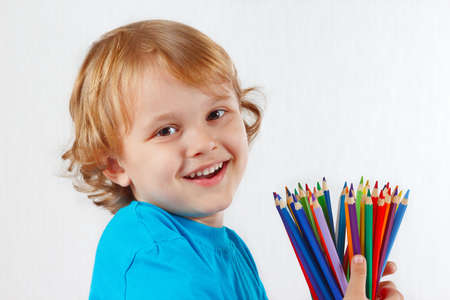 Smiling child with color pencils on a white background  photo