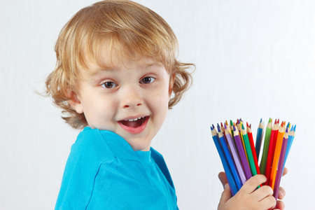 Little cute child holds color pencils on a white background photo