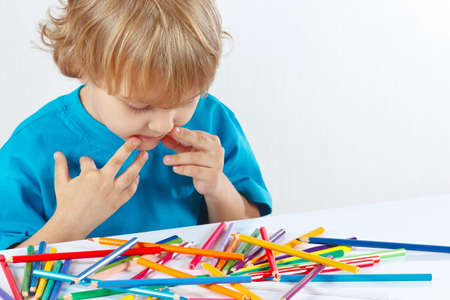 Little boy at the table with color pencils on a white background photo