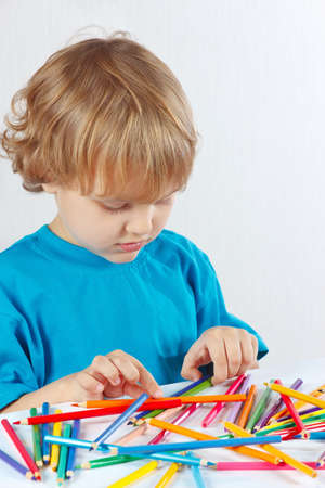 Young cute blond boy at the table with color pencils on a white background photo