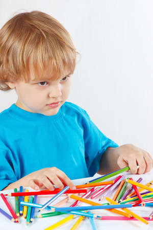 Young blond boy at the table with color pencils on a white background photo