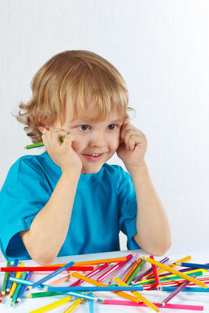 Young cute boy at the table with color pencils on a white background photo