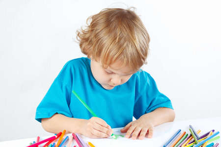 Little cute boy draws with color pencils on a white background photo