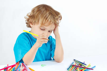 Young blond boy draws with color pencils on a white background photo