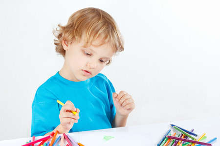 Young cute boy draws with color pencils on a white background photo