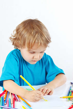 Little child draws with color pencils on a white background photo