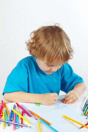 Cute child draws with color pencils on a white background photo