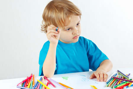 Little cute child draws with color pencils on a white background photo