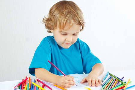 Little boy draws with color pencils on a white background photo