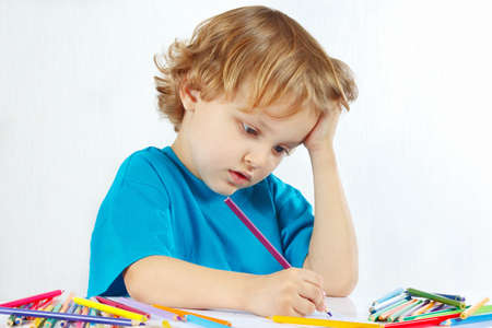 Young cute blond boy draws with color pencils on a white background photo