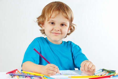 Little smiling boy draws with color pencils on a white background photo