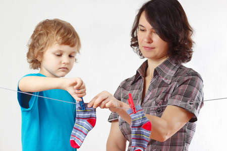 A little boy helps her mother to hang up your clothes photo
