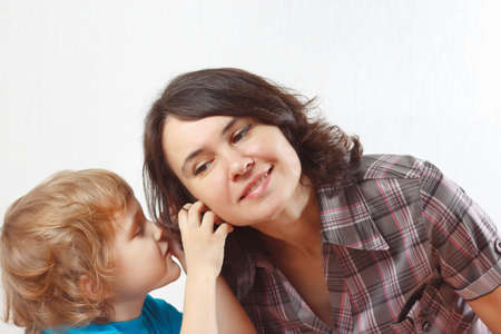 A little boy whispers something to his mother photo