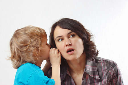 A little boy whispers to his mother something into her ear