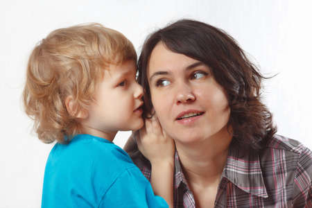 niños platicando: Joven muchacho rubio susurra algo a su madre en un fondo blanco Foto de archivo
