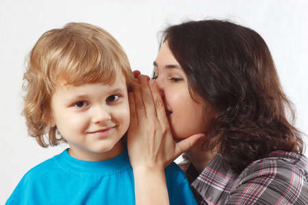 Mother whispers something to her little son Stock Photo