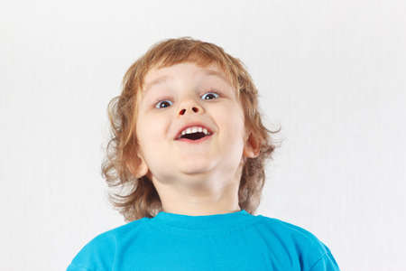 Little boy with the emotion of surprise on a white background photo