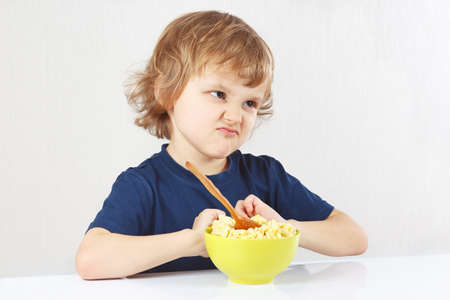 refusing: Little cute blonde boy refuses to eat a porridge