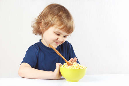 Little cute blonde boy refuses to eat a cereal  photo