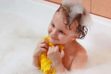 washcloth: Little blond boy with a washcloth bathes in the bathroom Stock Photo