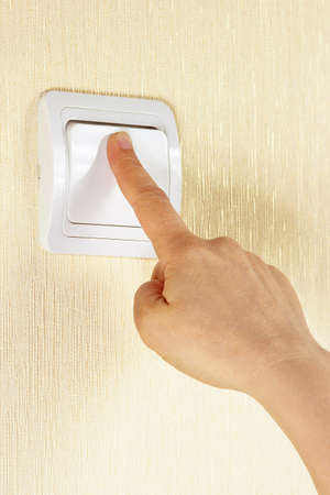 Hand presses the light switch on wall photo