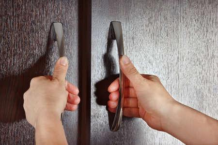 Women s hands are open cabinet, dark wood photo