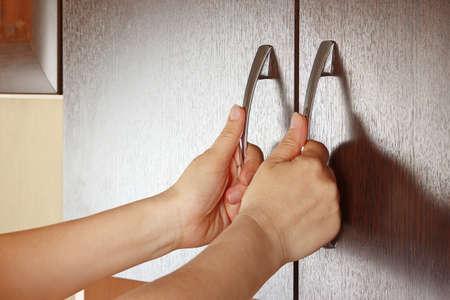 Women s hands closed cabinet doors, dark wood Stock Photo