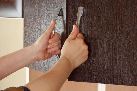 Women s hands are open the cupboard doors, dark wood photo