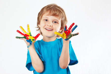 Smiling boy with painted hands on a white background photo