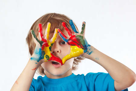Little blond boy with painted hands on a white background