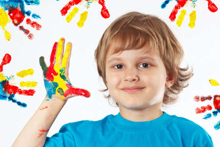 Young boy with painted hands on a background of hand prints Stock Photo