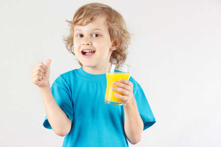 Little blonde boy is going to drink a fresh orange juice on white background Stock Photo