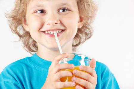 Little smiling boy drinking a fresh orange juice on white background photo