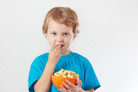 Young child eating popcorn on a white background photo