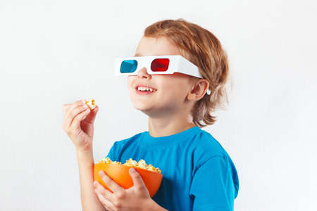 Young smiling boy in stereo glasses eating popcorn on white background