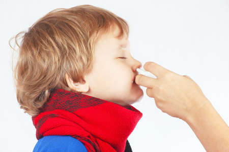 Little sick boy used nasal spray in the nose on a white  Stock Photo
