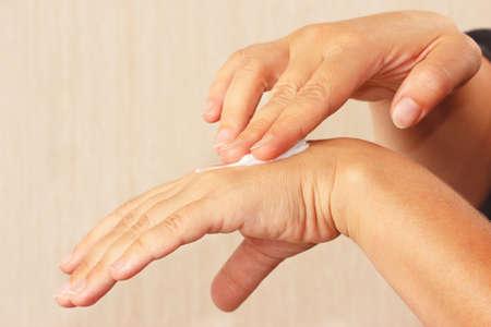 Female hands using a cosmetic skin cream