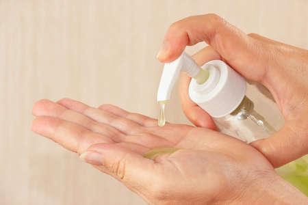 Female hands applying antibacterial liquid soap close up
