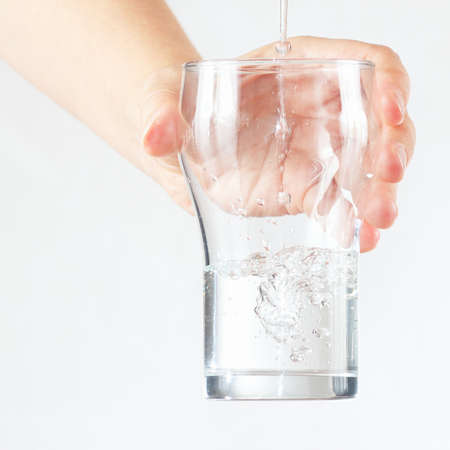 Female hand holding a glass of fresh water is poured on white background photo