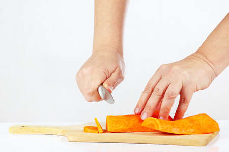 Women s hands with a knife chops carrot on a cutting board photo
