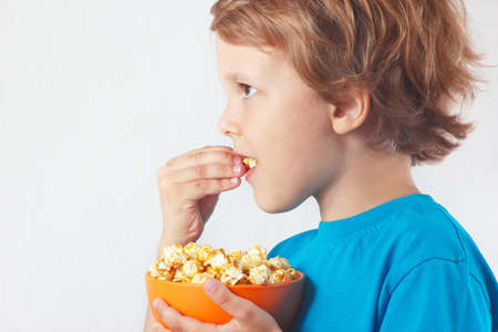 Cut child eating popcorn on a white background photo