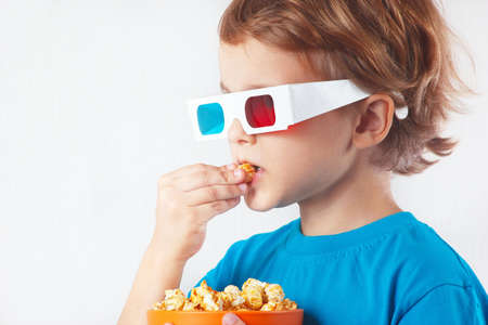 ironic: Young ironic boy in stereo glasses eating popcorn on white background Stock Photo