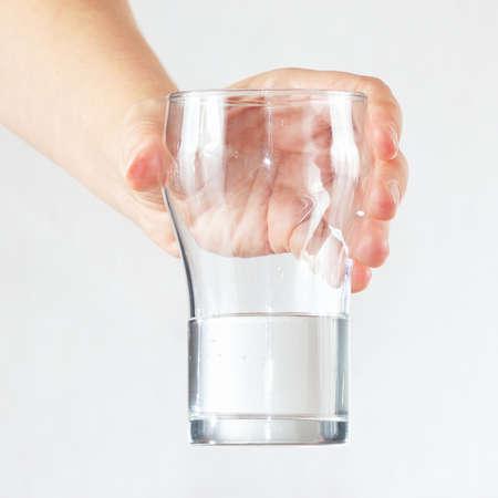 gocce di acqua: Mano femminile in possesso di un bicchiere di acqua fresca su sfondo bianco Archivio Fotografico