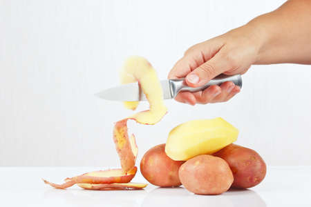 Female hands peeling fresh potatoes with a knife on a white background