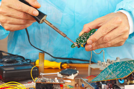 Repair electronic board of device with a soldering iron in the service workshop photo