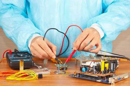 Master checks board of electronic device with a multimeter in the service workshop